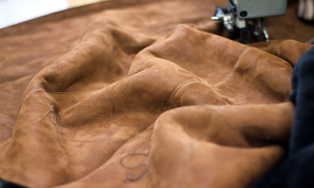 A sewing machine putting together a large patch of vegan leather