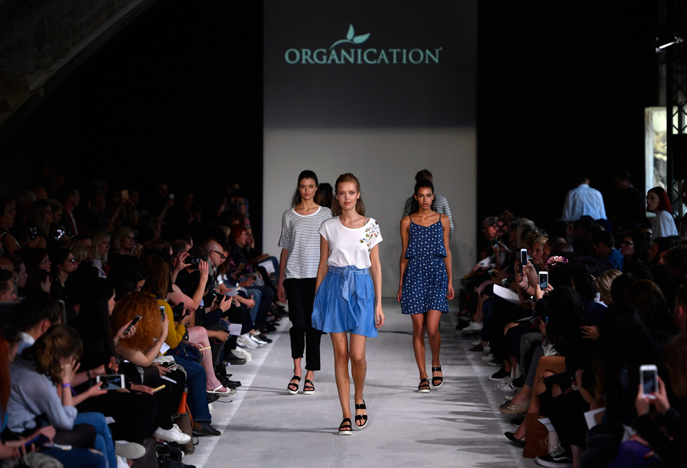 Three girls walking on a fashion catwalk, for a sustainable fashion brand called Organication.