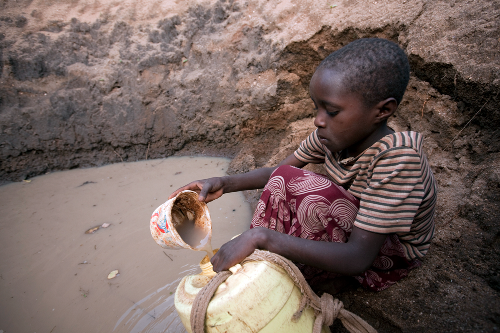 African child filling up a white container with dirty water poured from a dirty plastic cup.