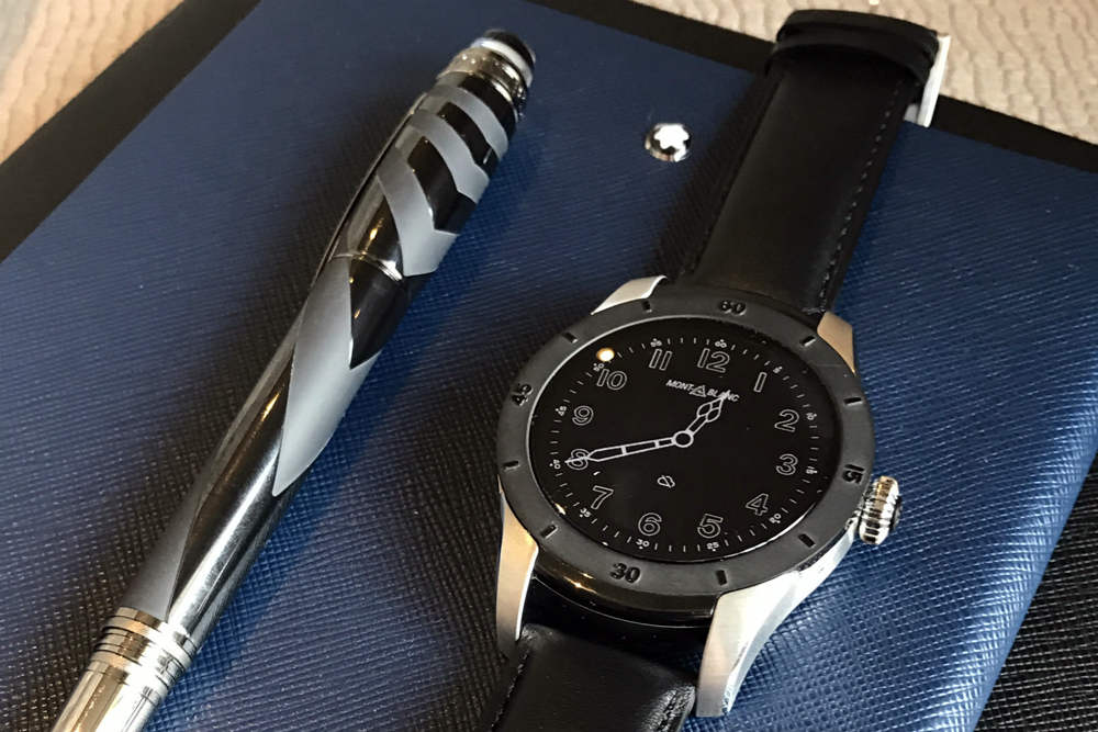 Luxury Smartwatches: Montblanc Summit and plantinum montblanc pen on a blue leather wallet from montblanc