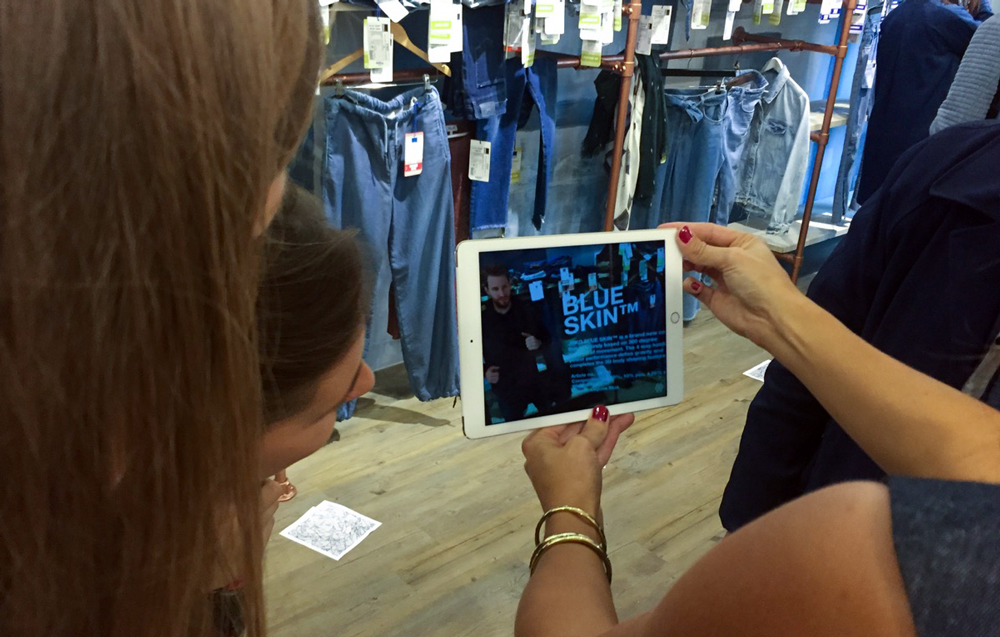 Three women using Fashion RetailTech on an Ipad to get more informations out of blue skin jeans