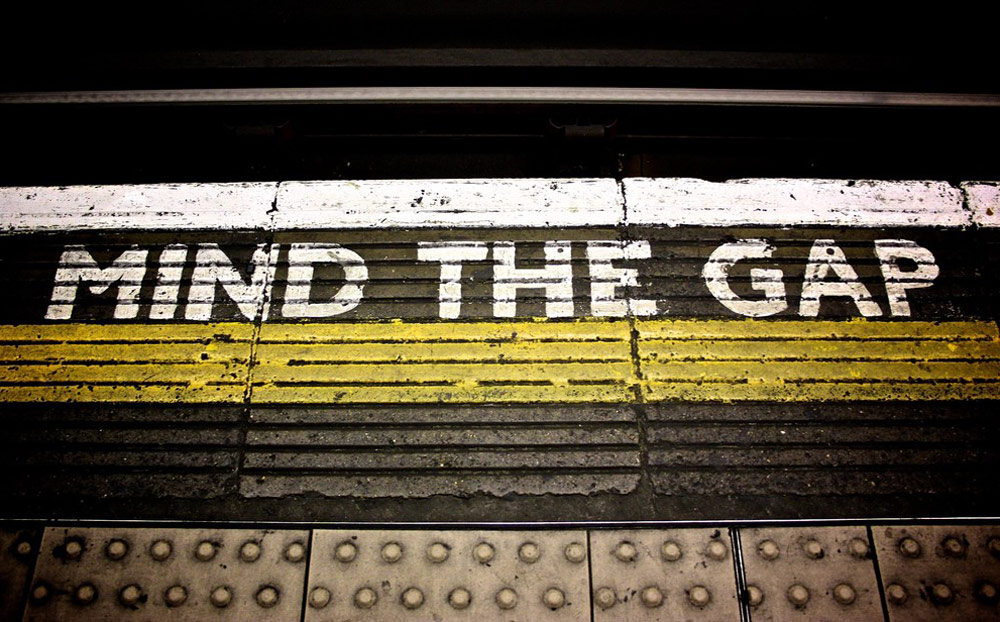 Sustainable Fashion Products Consumption - mind the gap sign from London underground