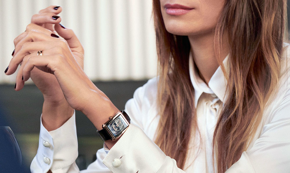 Chanel Calibre 4 Watch - woman wearing white shirt and a black chanel calibre 3 watch on her left werist