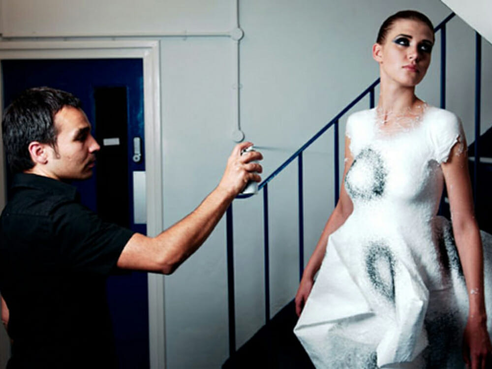Fabrican Sprayable Clothes - man in black spraying a dress on a woman's body