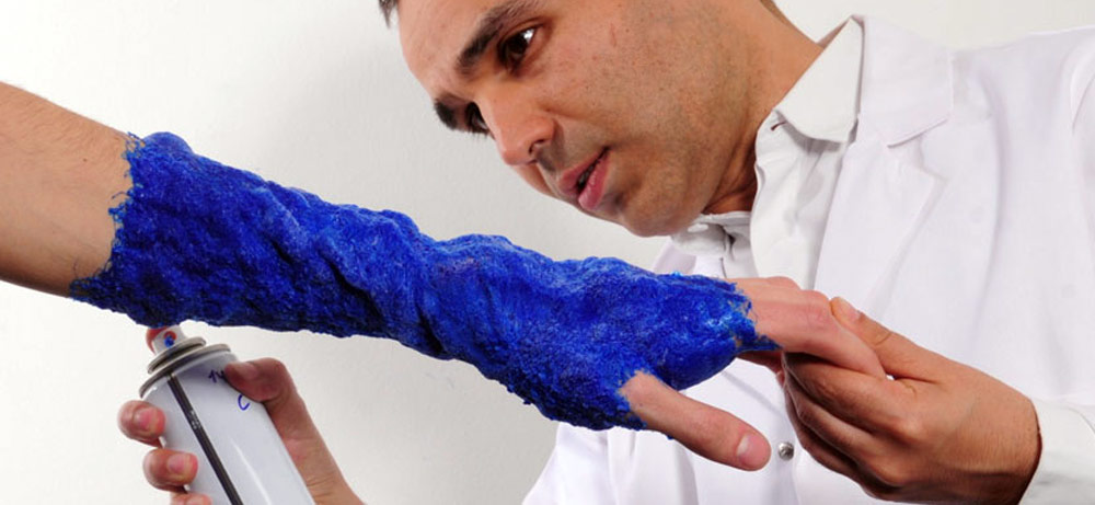 Fabrican Sprayable Clothes - Dr Manel Torres straying blue textile on a woman's arm