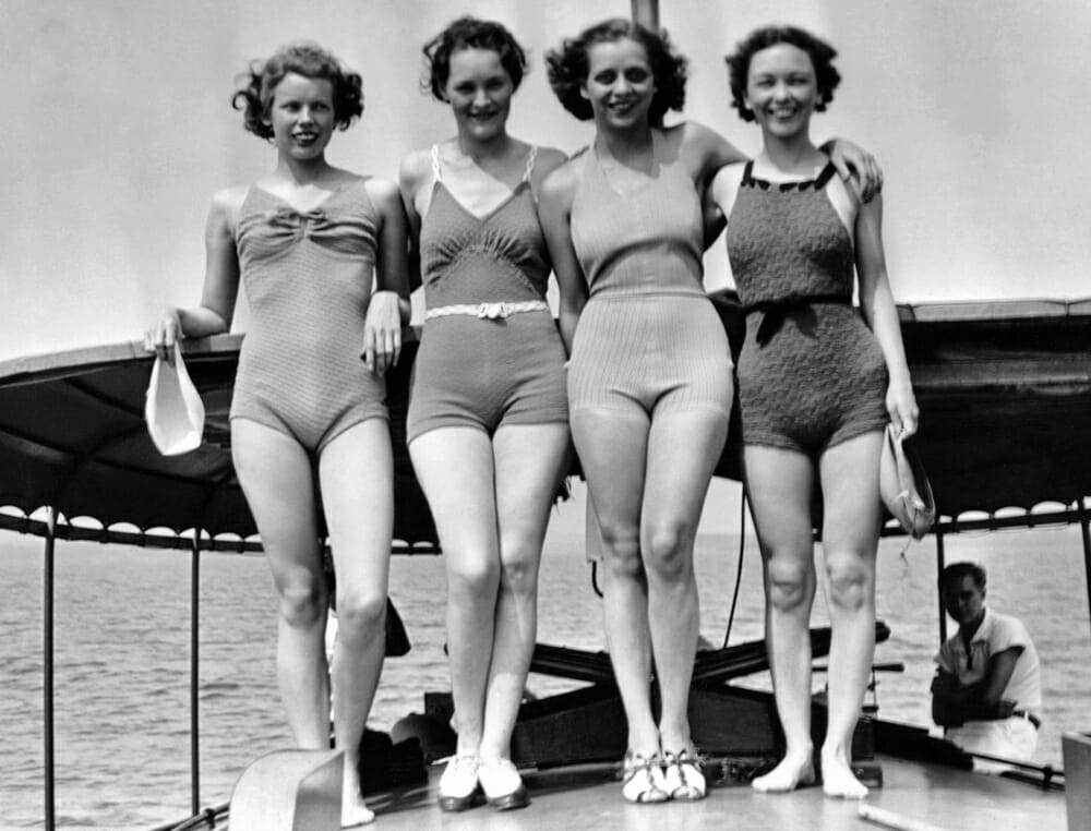 The evolution of swimwear - women in bathing suits standing on boat deck