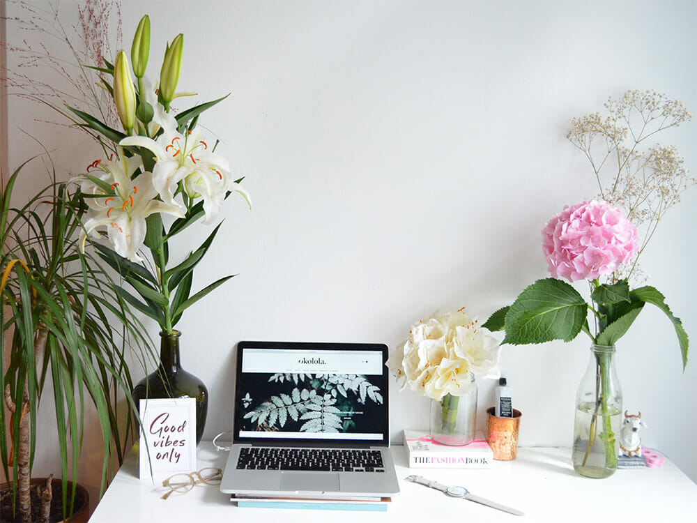 The ultimate guide to vegan living by shagun, computer on a desk with plants and flowers